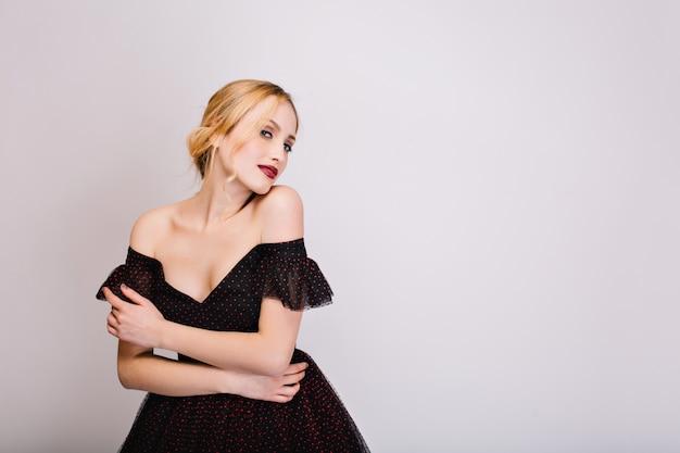 Close-upportret van aantrekkelijk blond meisje dat sensueel kijkt, zich goed voelt, poseren. ze heeft een mooie zachte huid en kapsel met krul. het dragen van zwarte jurk met open schouders. geïsoleerd.