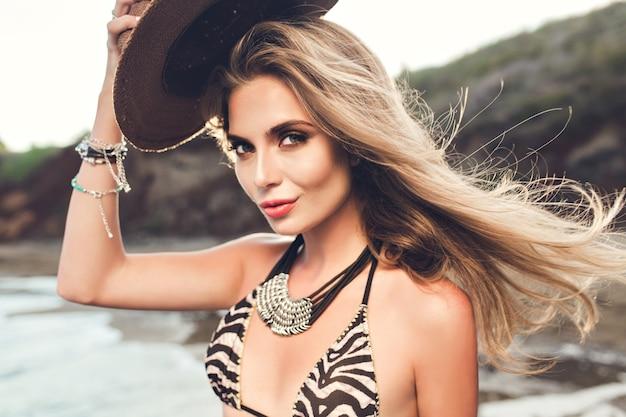 Close-upportret van aantrekkelijk blondemeisje met lang haar die op strand op zonsondergangachtergrond stellen. ze houdt de hoed boven en kijkt naar de camera.
