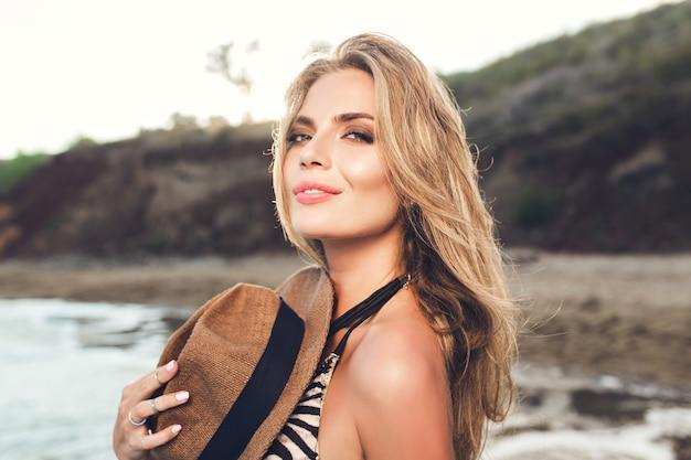 Close-upportret van aantrekkelijk blondemeisje met lang haar die zich voordeed op strand. ze houdt hoed op bikini en kijkt naar de camera.