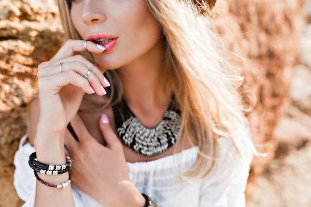 Close-upportret van aantrekkelijk blondemeisje met lang haar op rotsachtergrond. ze houdt de vinger op de lippen.