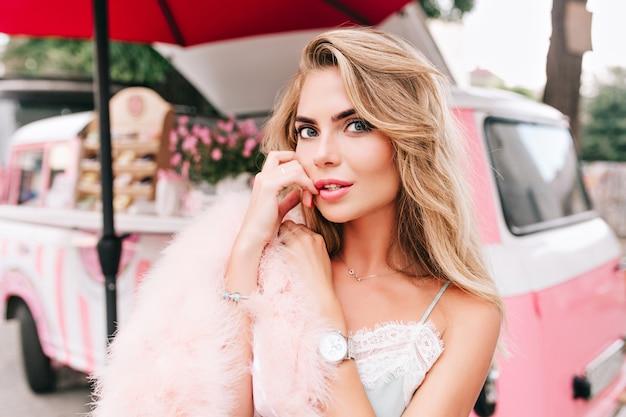 Close-upportret van aantrekkelijk pin-up blond meisje op retro koffieauto achtergrond. ze houdt de vinger op de lippen, kijkt naar de camera.