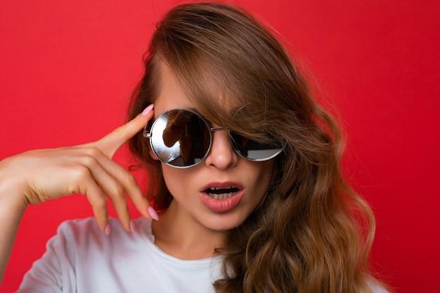Close-upportret van aantrekkelijke sexy jonge blondevrouw die alledaagse modieuze kleding en modern draagt