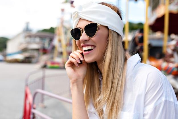 Close-upportret van aantrekkelijke vrij gelukkige vrouw met blonde haren en prachtige glimlach die zich voordeed op camera in de stad. jonge mooie hipster vrouwen, streetstyle, blij