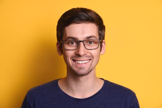 Close-upportret van aantrekkelijke vrolijke kerel in oogglazen die gelukkig glimlachen geïsoleerd over gele studioachtergrond