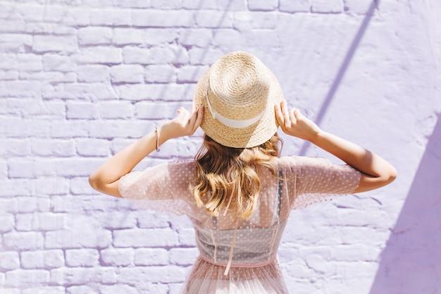 Close-upportret van achterkant van slank romantisch meisje in lichte kleding die oude muur bekijken
