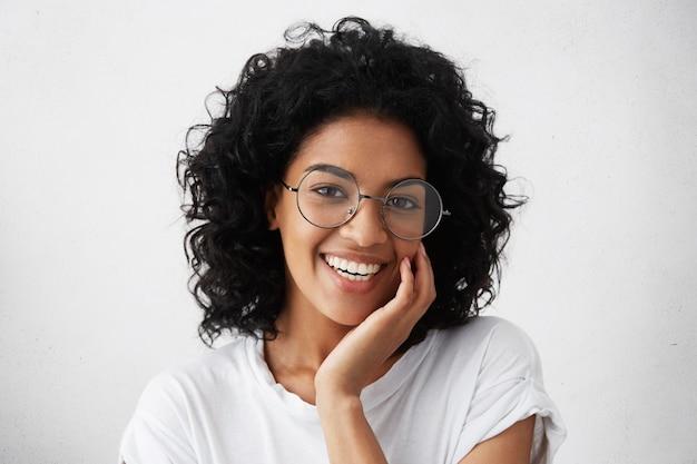 Close-upportret van afro-amerikaanse vrouw met donker krullend borstelig haar dat een bril draagt