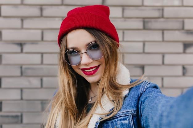 Close-upportret van betoverende sensuele vrouw met rode lippen. verfijnd kaukasisch meisje dat de lentemorgen buiten doorbrengt.