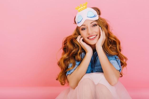 Close-upportret van bevallig mooi meisje met dromerige gezichtsuitdrukking wat betreft haar wangen geïsoleerd op roze achtergrond. schattige krullende jonge vrouw in slaapmasker ontwaakt en plezier in haar kamer