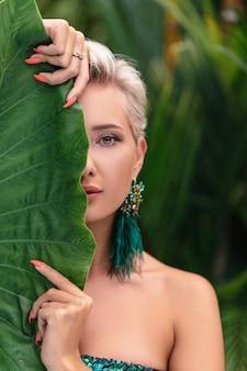 Close-upportret van blauwogig meisje die speels met installatie stellen. foto van charmante verlegen blonde dame verbergend gezicht achter groen blad.