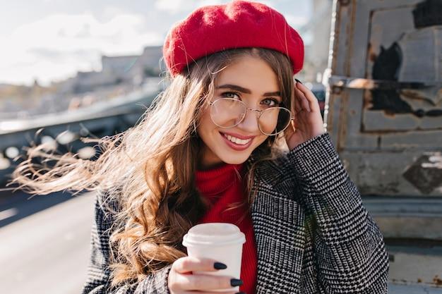 Close-upportret van blauwogige blanke vrouw met oprechte glimlach die zich voordeed op stedelijke achtergrond in de ochtend