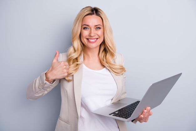 Close-upportret van blije dame die in handen laptop houdt die duim toont