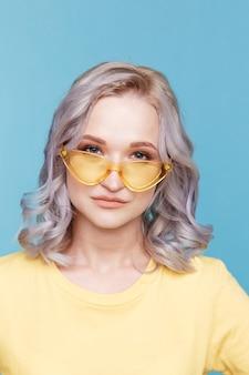 Close-upportret van blond wijfje in de gele kleren en de zonnebril die over de blauwe achtergrond wordt geïsoleerd.