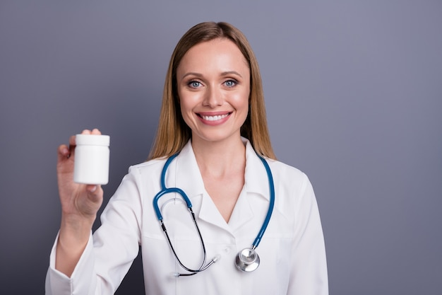 Close-upportret van blondemeisje ervaren doc die drugsfles aanbeveelt