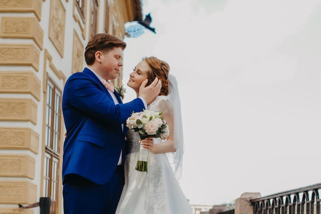 Close-upportret van bruid en bruidegom op een blauwe hemelachtergrond