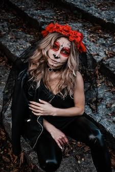 Close-upportret van calavera catrina. jonge vrouw met de make-up van de suikerschedel. dia de los muertos. dag van de doden. halloween. santa muerte make-up vrouw op halloween vooravond