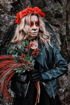 Close-upportret van calavera catrina. jonge vrouw met de make-up van de suikerschedel en rode bloemen. dia de los muertos. dag van de doden. halloween. santa muerte make-up vrouw op halloween vooravond. mode creatief