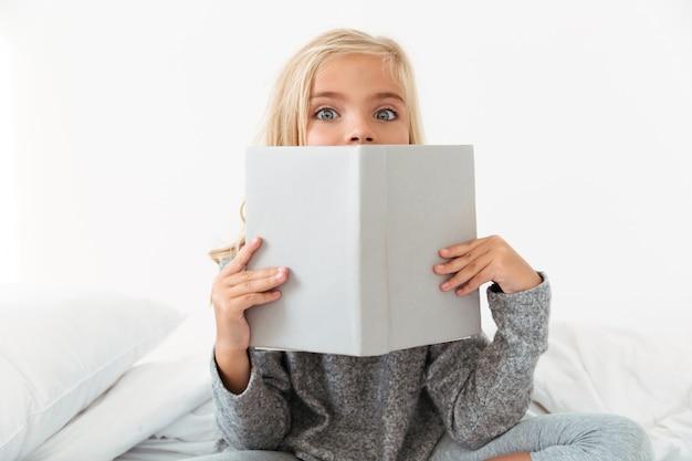 Close-upportret van charmant meisje die haar gezicht behandelen met boek,