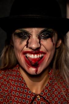 Close-upportret van clownvrouw die haar tong uit plakt