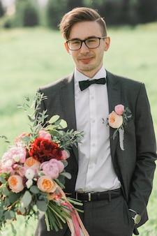 Close-upportret van de bruidegom met een boeket voor de bruid. een jonge man in pak en bril