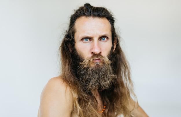 Close-upportret van de ernstige gebaarde mens met emotioneel gezicht, lang haar en snor het stellen voor beelden, geïsoleerde achtergrond. hipster heeft een nieuw kapsel nodig