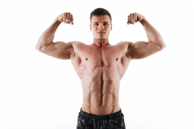 Close-upportret van de ernstige sterke sportenmens die zijn bicepsen tonen