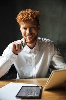Close-upportret van de jonge gelukkige krullende mens van readhead, die bij houten lijst zitten, die groene pan houden, het kijken