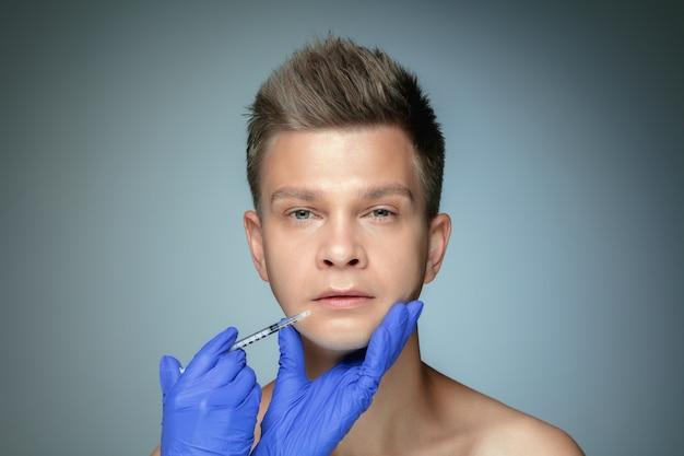 Close-upportret van de jonge mens die op grijze studiomuur wordt geïsoleerd bij het vullen van chirurgieprocedure