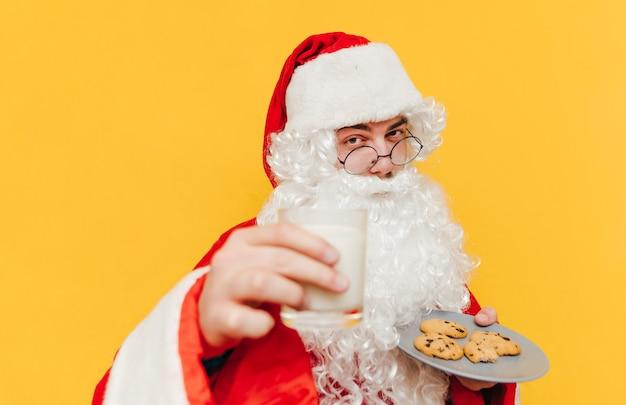 Close-upportret van de kerstman op een gele achtergrond met een glas melk