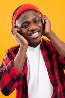 Close-upportret van de knappe afrikaanse mens die in rood geruit overhemd aan muziek op hoofdtelefoons luisteren