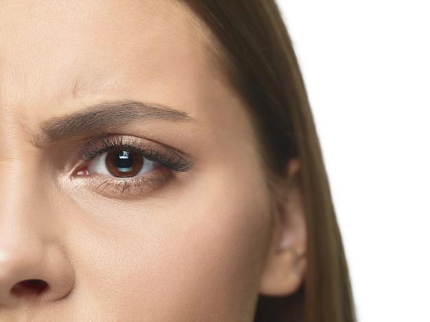 Close-upportret van de ogen en het gezicht van de jonge vrouw met rimpels.