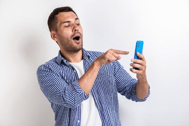 Close-upportret van de wondermens die aan het smartphonescherm richten