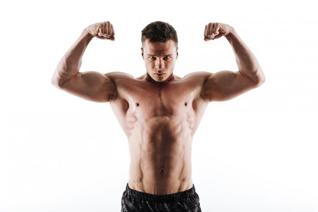 Close-upportret van de zwetende sterke sportenmens die zijn bicepsen toont