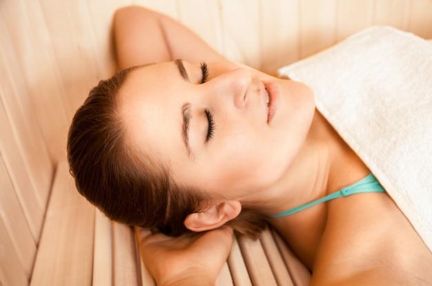 Close-upportret van donkerbruine vrouw die met gesloten ogen bij sauna ligt