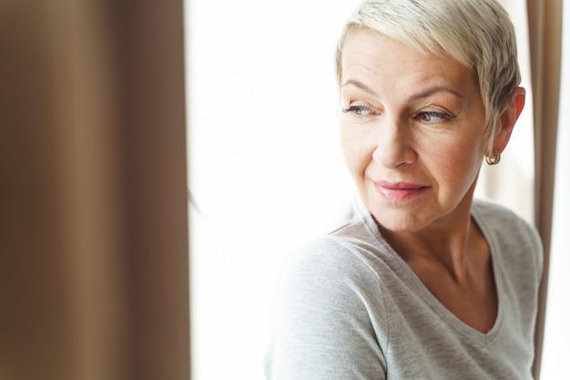 Close-upportret van een aantrekkelijke dromerige hogere kaukasische dame met een kort kapsel die opzij kijken