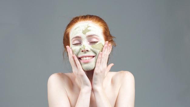 Close-upportret van een charmante jonge vrouw met kosmetische klei op haar gezicht wat betreft haar wang tijdens een huidzorgprocedure