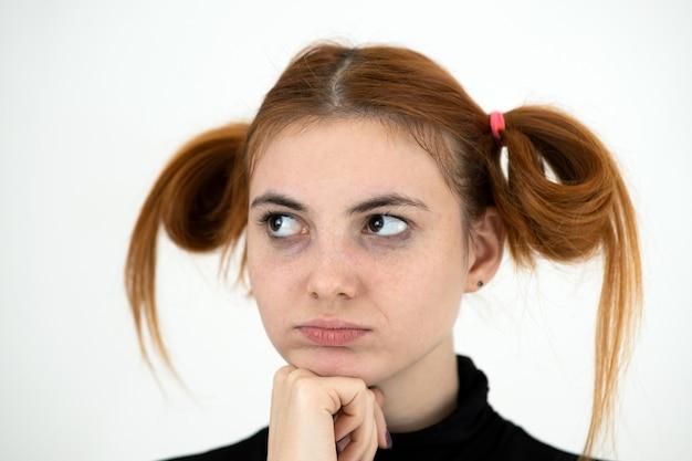 Close-upportret van een droevige roodharige tiener die met kinderachtig kapsel beledigd kijkt.