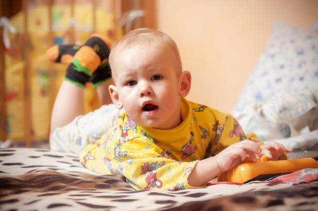 Close-upportret van een ernstig jongetje van een jaar in een natuurlijke en eenvoudige thuisomgeving. het concept van een actieve en gezonde levensstijl van een kind.