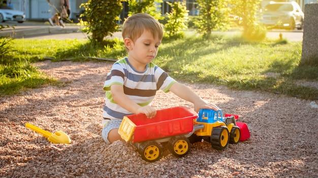 Close-upportret van een gelukkig lachende 3 jaar oude kindjongen die zand graaft op de speelplaats met speelgoed plastic vrachtwagen of graafmachine
