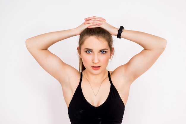Close-upportret van een geschiktheidsvrouw op wit. sterke armen en schouders van een sportief meisje