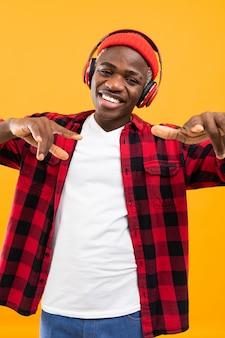 Close-upportret van een glimlachende knappe afrikaan in een rood geruit overhemd dat aan muziek met hoofdtelefoons op een gele studioachtergrond luistert