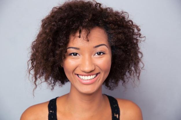 Close-upportret van een glimlachende vrouw over grijze muur
