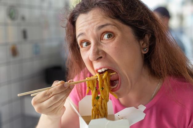 Close-upportret van een grappig gek jong mooi meisje dat chinese noedels met houten eetstokjes eet