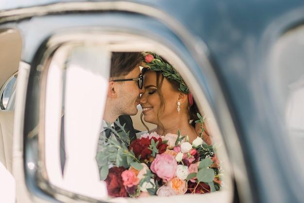 Close-upportret van een houdend van paar van man en vrouw op hun huwelijksdag in een auto. de bruid en bruidegom kussen.