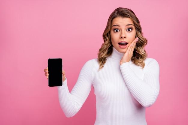 Close-upportret van een innemend, behoorlijk verbaasd meisje dat een telefoon met een zwart scherm demonstreert