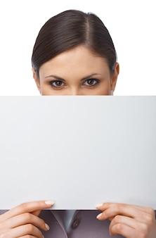 Close-upportret van een jong meisje dat zich achter een leeg wit aanplakbord verstopt, dat op wit wordt geïsoleerd