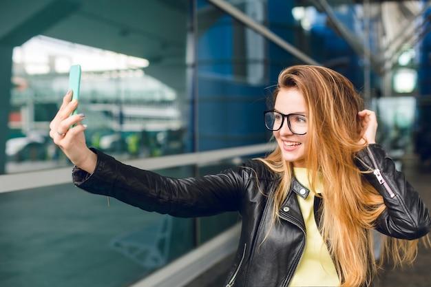 Close-upportret van een jong meisje dat zich buiten in luchthaven bevindt. ze heeft lang haar, een zwarte jas en een bril. ze maakt een selfie-portret.