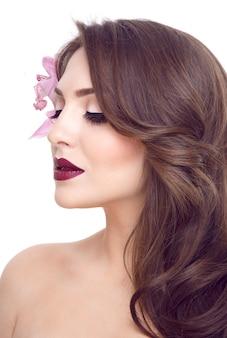 Close-upportret van een jong model met golvend haar en purpere orchidee daarin, kapsel
