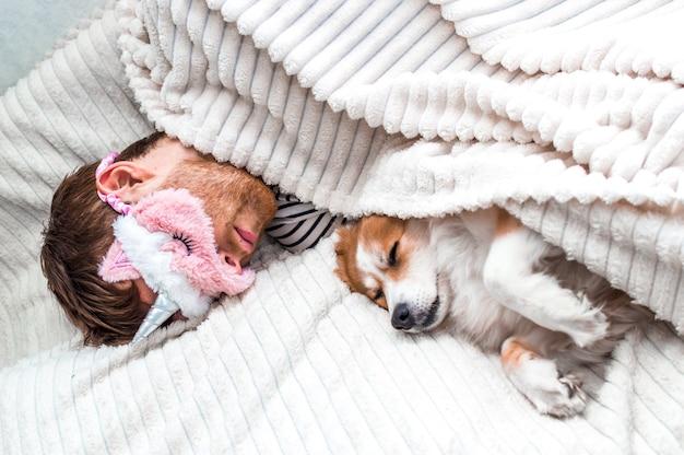 Close-upportret van een jonge man met een roze masker die slaapt in een bed onder een kleed met zijn hond