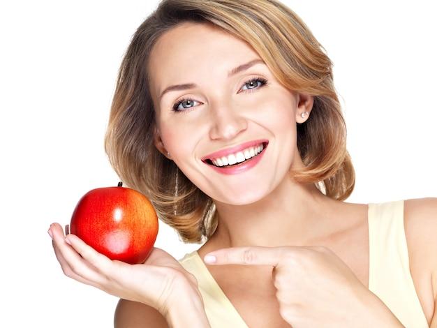 Close-upportret van een jonge mooie glimlachende vrouw die de vinger richt op appel die op wit wordt geïsoleerd.