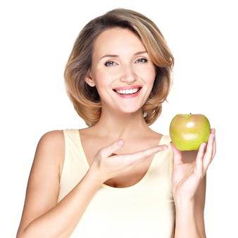 Close-upportret van een jonge mooie glimlachende vrouw die op appel richt - dat op wit wordt geïsoleerd.
